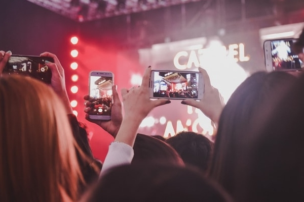 a crowd of content ambassadors holding smartphones to record a concert